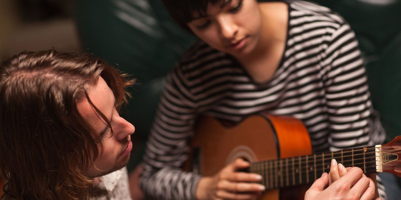 21818227-young-musician-teaches-female-student-to-play-the-guitar---3000x1500-compressor.jpg